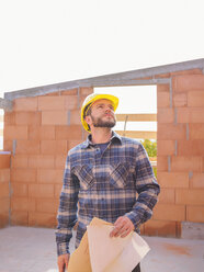 Portrait of foreman with construction plan checking work at construction site - LAF001542
