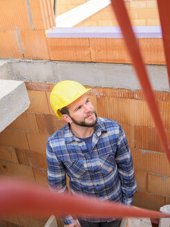 Portrait of foreman checking work at construction site - LAF001548