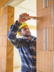 Foreman with construction plan  checking construction work with pocket rule - LAF001551