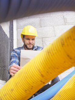 Foreman with construction plan  at construction site - LAF001554