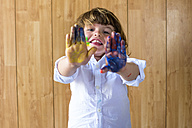 Portrait of smiling little boy showing his palms full of finger colours - KIJF000006