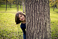 Portrait of girl hiding behind tree trunk - LVF004144