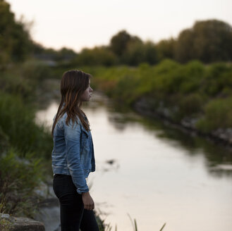 Portrait of teenage girl standing at riverside - HCF000157