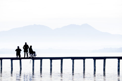 Germany, Seebruck, silhouettes of three persons on a wooden boardwalk at Chiemsee - HAM000091