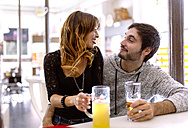 Young couple with beverages relaxing in a pub - MGOF001015