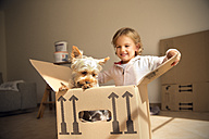Smiling girl with dog inside cardboard box - TOYF001419