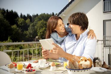 Happy couple having breakfast on balcony - TOYF001422