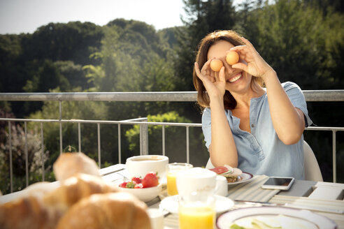 Playful woman having breakfast on balcony - TOYF001428