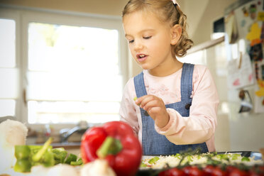 Girl in kitchen preparing pizza - TOYF001434