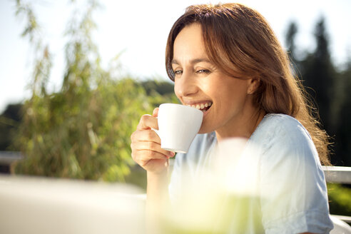 Happy woman on balcony with cup of coffee and laptop - TOYF001440