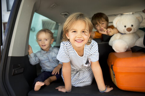 Happy kids in car boot with teddy - TOYF001443
