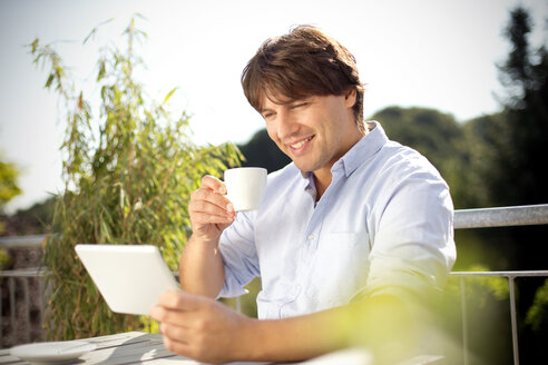 Smiling man with digital tablet and cup of coffee on balcony - TOYF001446