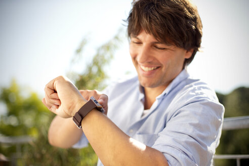 Smiling man outdoors looking at smartwatch - TOYF001452