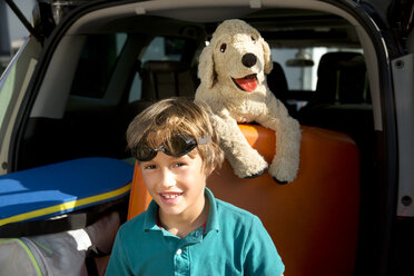 Smiling boy in car boot with swimming goggles and cuddly toy - TOYF001458