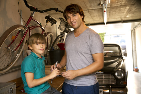 Father and son in garage with vintage car and tools - TOYF001461