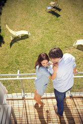 Happy couple standing on balcony above garden - TOYF001464