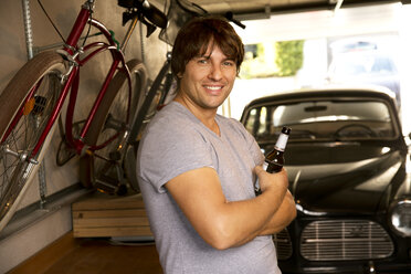 Smiling man in garage with bottle of beer and vintage car - TOYF001467