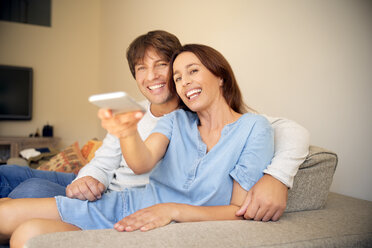 Smiling couple on couch watching TV - TOYF001479
