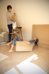 Laughing woman in cardboard box with man painting wall - TOYF001488