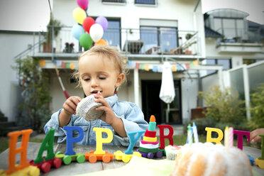 Happy toddler celebrating birthday in garden - TOYF001491