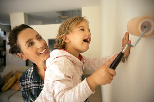 Happy woman with daughter painting a wall - TOYF001497