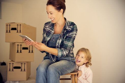 Laughing woman with daughter looking at digital tablet with cardboard boxes in background - TOYF001503