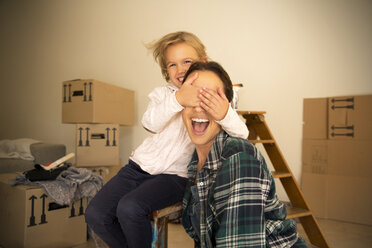 Daughter covering mother's eyes with cardboard boxes in background - TOYF001509
