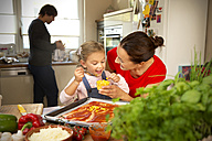Happy mother and daughter in kitchen preparing pizza with father in background - TOYF001515