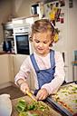 Girl in kitchen preparing pizza - TOYF001518