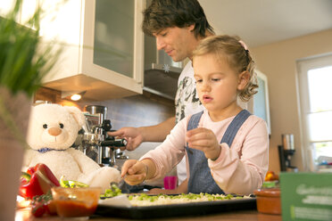 Father and daughter in kitchen preparing pizza - TOYF001521