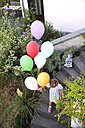 Girl walking on stairs holding colorful balloons - TOYF001524