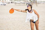 Spain, Cadiz, El Puerto de Santa Maria, Woman playing frisbee on the beach - KIJF000010