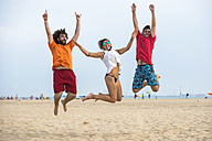 Spain, Cadiz, El Puerto de Santa Maria, Friends jumping on the beach - KIJF000013