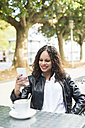 Portrait of smiling young woman sitting in a street cafe looking at her smartphone - RAEF000625