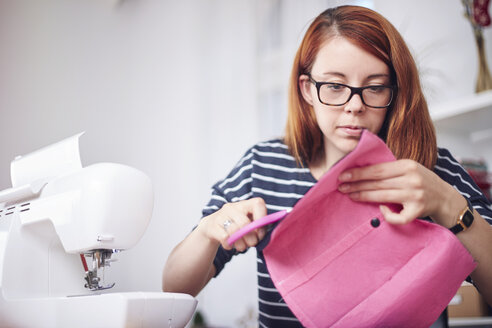 Portrait of young woman cutting pink fabric at home - SEGF000420