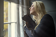 Woman and her cat looking through the window at home - FRF000354