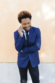 Portrait of smiling young businessman telephoning with smartphone - EBSF001008