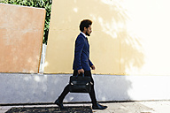 Young businessman with briefcase walking on pavement - EBSF001011