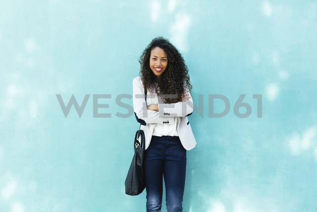 Portrait of smiling young businesswoman with leather bag standing in front of a blue wall - EBSF001020
