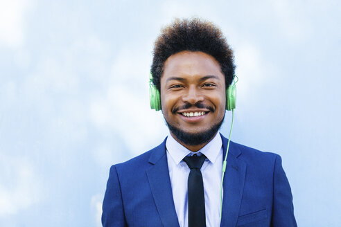 Portrait of smiling young businessman hearing music with headphones - EBSF001023