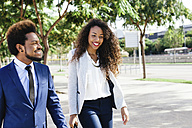 Spain, Barcelona, portrait of two smiling young business people walking side by side - EBSF001026