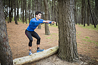 Athlete exercising box jumps in forest - RAEF000627