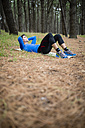 Athlete exercising sit ups in forest - RAEF000630