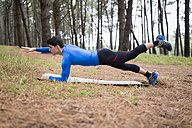 Athlete exercising planks in forest - RAEF000633
