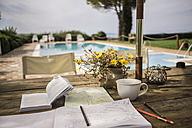 Italy, Tuscany, Guidebook, map and notebook on table by the pool - RIB000384