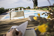 Italy, Tuscany, Person reading book, sitting at table by the pool - RIBF000387