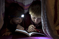 Brother and sister reading book under a blanket - SARF002303
