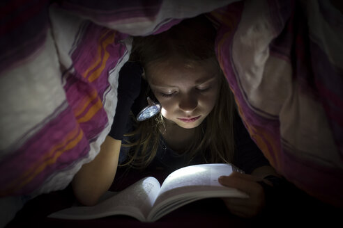Little girl with torch reading book under a blanket - SARF002306