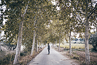 Spain, Tarragona, back view of young man with longboard on autumnal country road - JRFF000176