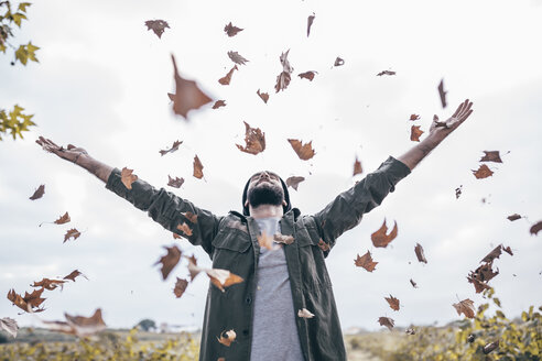 Young man throwing autumn leaves in the air - JRFF000182